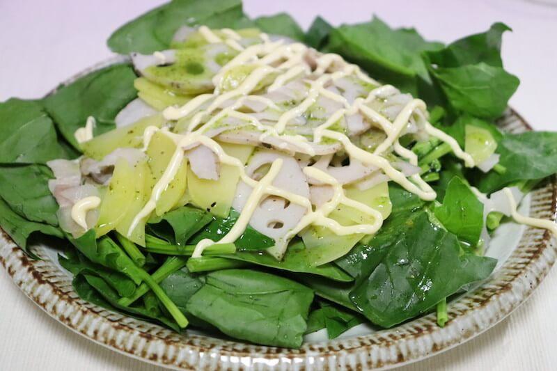 カットしたほうれん草をお皿に敷いて、温めた根菜類を上にのせてグリーンハーブソースをかけてマヨネーズを絞りかける