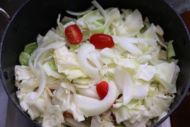 鍋に野菜を半分敷き詰めてその上に混ぜ合わせた肉だねを入れて、その上から残りの野菜を敷き詰める