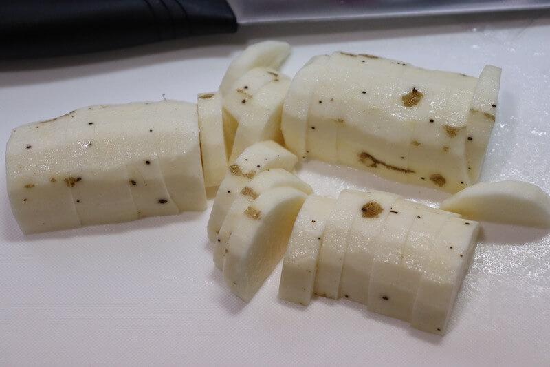 やまと芋のひげ根をとるようにゴシゴシ洗って皮ごと1cm厚の半月切りにする