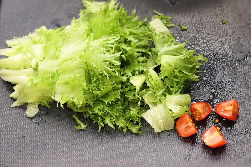 フリルレタスは食べやすい大きさに切り、トマトは4等分のくし切りにする。